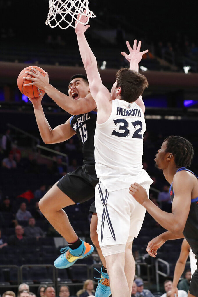 Xavier forward Zach Freemantle (32) defends against DePaul guard Oscar Lopez Jr. (15) during the second half of an NCAA college basketball game in the first round of the Big East men's tournament Wednesday, March 11, 2020, in New York. DePaul won 71–67. (AP Photo/Kathy Willens)