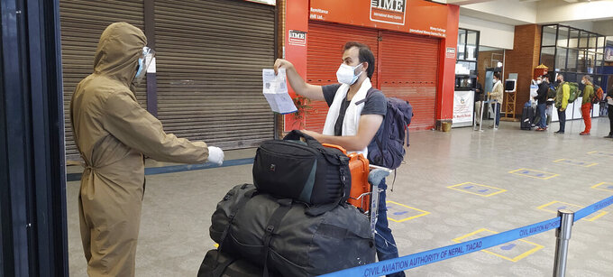 A stranded Spanish national shows his papers as he arrives to board a repatriation flight arranged by their government at Kathmandu airport, Nepal, Friday, May 21, 2021,. The flight to Madrid took 96 people who have been stranded in Nepal since the country went on lockdown in April to curb the spiking COVID-19 cases. The plane also brought to Nepal medical aid and equipment worth 1 million Euro ($1.2 million) gifted by the Spanish government as Nepal struggles with highest daily new cases and highest daily deaths this month. (AP Photo/Binaj Gurubacharya)