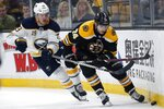 Buffalo Sabres' Jake McCabe (19) battles Boston Bruins' Jake DeBrusk (74) for the puck during the second period of an NHL hockey game in Boston, Saturday, Jan. 5, 2019. (AP Photo/Michael Dwyer)