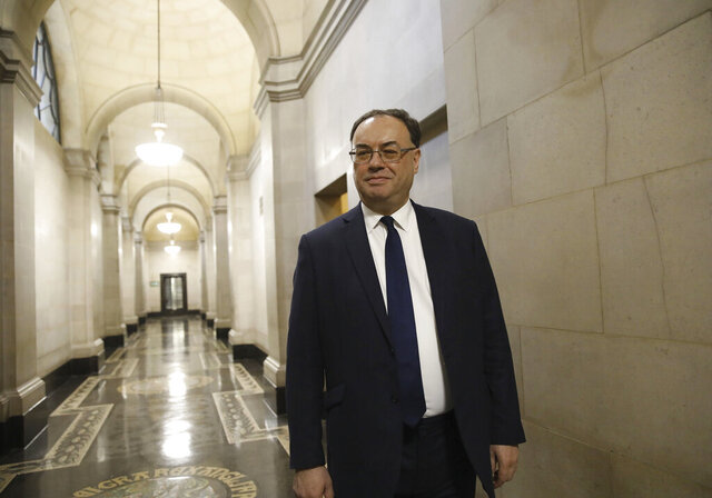 FILE - In this file photo dated Monday March 16, 2020, The Bank of England Governor Andrew Bailey poses for a photograph at the central bank in London.  The Bank of England slashed its key interest rate to 0.1%, on Thursday March 19, 2020, its lowest-ever level, amid global economic turmoil sparked by the coronavirus pandemic. For some people the COVID-19 coronavirus causes mild or moderate symptoms, but for some it causes severe illness.(Tolga Akmen/AP, FILE)