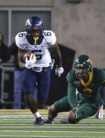 West Virginia running back Kennedy McKoy (6) runs past Baylor linebacker Blake Lynch (2) during the first half of an NCAA college football game in Waco, Texas, Thursday, Oct. 31, 2019. (AP Photo/Jerry Larson)