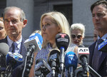 In this Aug. 27, 2019, photo, Virginia Roberts Giuffre, center, who says she was trafficked by sex offender Jeffrey Epstein, holds a news conference outside a Manhattan court where sexual assault claimants invited by a judge addressed a hearing following Epstein's jailhouse death in New York. Prince Andrew suffered fresh scrutiny Monday night, Dec. 2, when the woman who says she was a trafficking victim made to have sex with him when she was 17 asked the British public to support her quest for justice. (AP Photo/Bebeto Matthews)
