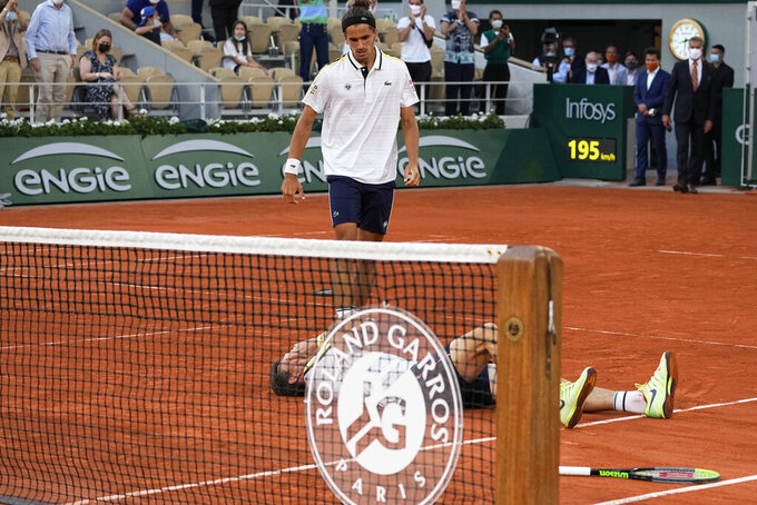 France's Nicolas Mahut lays on the clay as teammate Pierre-Hugues Herbert join him as they defeat Kazakstan's Alexander Bublik and Andrey Golubev in their men's doubles final match of the French Open tennis tournament at the Roland Garros stadium Saturday, June 12, 2021 in Paris. (AP Photo/Michel Euler)