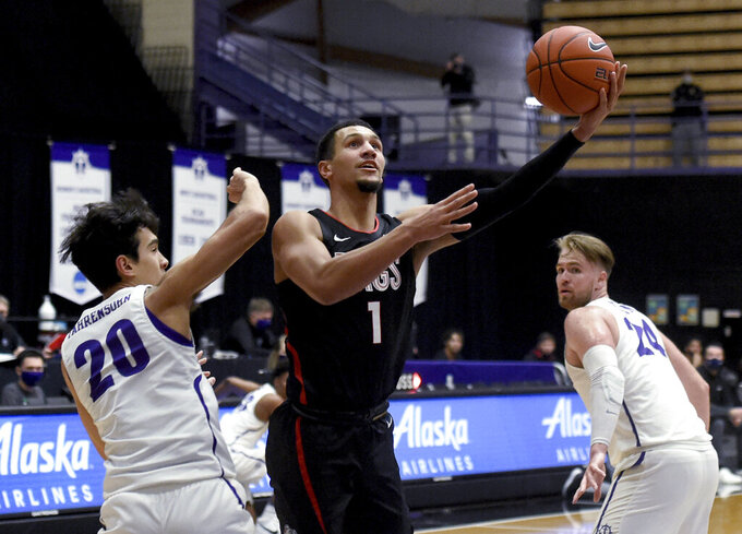 Gonzaga guard Jalen Suggs, center, drives to the basket on Portland guard Takiula Fahrensohn, left, as Portland forward Mikey Henn, right, watches during the first half of an NCAA college basketball game in Portland, Ore., Saturday, Jan. 9, 2021. (AP Photo/Steve Dykes)