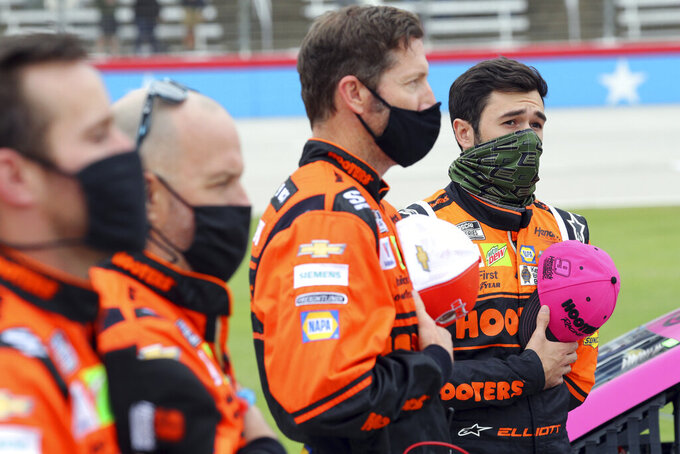 Chase Elliott (9, right) and his crew stand for the National Anthem before a NASCAR Cup Series auto race at Texas Motor Speedway in Fort Worth, Texas, Sunday, Oct. 25, 2020. (AP Photo/Richard W. Rodriguez)