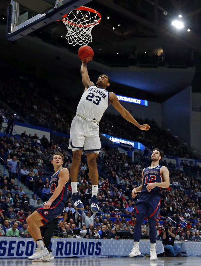 Villanova's Jermaine Samuels (23) goes in for a dunk against St. Mary's Tanner Krebs, left, and Tommy Kuhse (12) during the second half of a first round men's college basketball game in the NCAA Tournament, Thursday, March 21, 2019, in Hartford, Conn. (AP Photo/Elise Amendola)