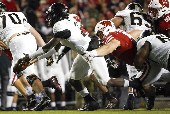 Wisconsin's Leo Chenal hits Army's Tyhier Tyler as he pitches the ball during the first half of an NCAA college football game Saturday, Oct. 16, 2021, in Madison, Wis. (AP Photo/Morry Gash)