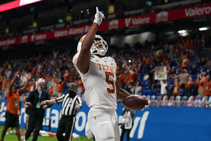 Texas running back Bijan Robinson celebrates after scoring a touchdown against Colorado during the first half of the Alamo Bowl NCAA college football game Tuesday, Dec. 29, 2020, in San Antonio. (AP Photo/Eric Gay)