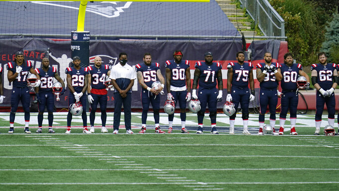"New England Patriots stand during the singing of ""Lift Every Voice and Sing"" before an NFL football game against the Miami Dolphins, Sunday, Sept. 13, 2020, in Foxborough, Mass. (AP Photo/Charles Krupa)"