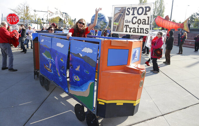 FILE - In this Oct. 17, 2013, file photo, a protester rides in a mock coal train as other protesters demonstrate against trains carrying coal for export moving through Washington state in Tacoma, Wash. The U.S. Supreme Court won't allow Wyoming and Montana to sue Washington for denying a key permit to build a coal export dock. Justices Clarence Thomas and Samuel Alito were in the minority in the ruling Monday, June 28, 2012, against letting the two states sue the third in a case that would have gone directly before the high court. (AP Photo/Ted S. Warren, File)