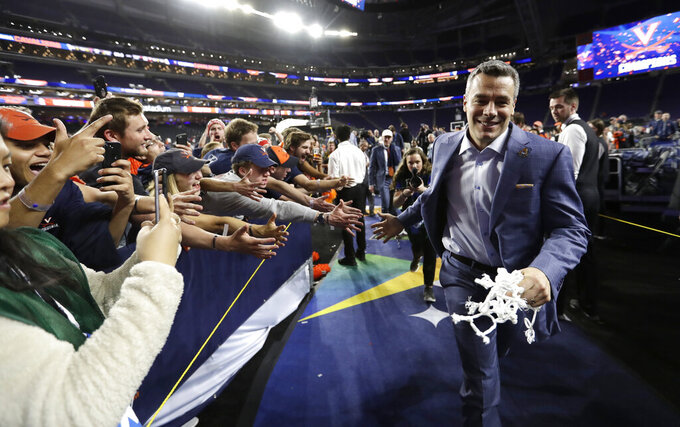 FILE- In this April 8, 2019, file photo, Virginia head coach Tony Bennett celebrates with fans after the championship game against Texas Tech in the Final Four NCAA college basketball tournament. (AP Photo/David J. Phillip, File)