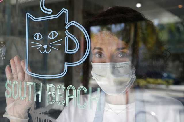 Celyta Jackson, owner of the Cat Cafe South Beach, looks out from her business during the coronavirus pandemic, Wednesday, July 29, 2020, in Miami Beach, Fla. The cafe offers a place for cat lovers to spend time with cats, which are also available for adoption. Jackson will be closing her business at the end of the week as the tourism sector in Miami-Dade County is suffering due to the pandemic. (AP Photo/Lynne Sladky)