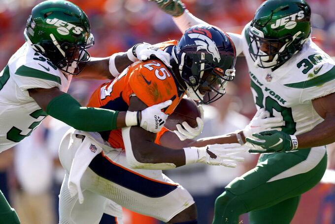 Denver Broncos running back Melvin Gordon (25) is tackled by New York Jets cornerback Michael Carter II (30) and New York Jets running back Michael Carter during the first half of an NFL football game, Sunday, Sept. 26, 2021, in Denver. (AP Photo/David Zalubowski)