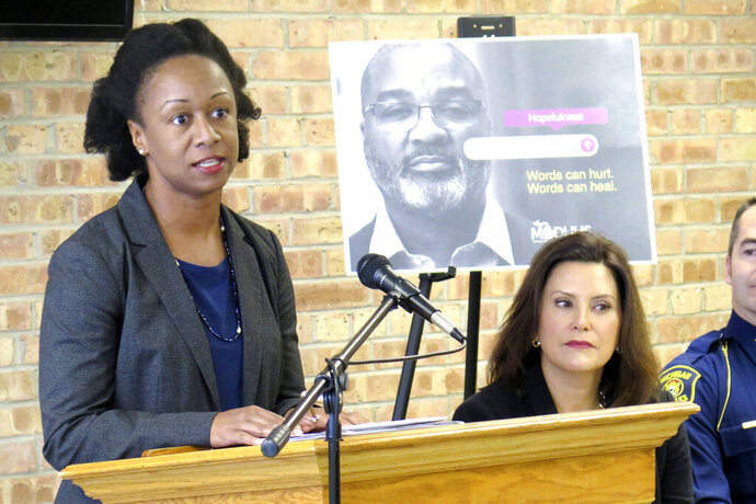 Dr. Joneigh Khaldun, left, Michigan's chief medical executive and the chief deputy for health at the state Department of Health and Human Services, announces initiatives to cut the number of opioid overdose deaths in half within five years during a news conference with Gov. Gretchen Whitmer, Thursday, Nov. 14, 2019, at the Forest Community Health Center in Lansing, Mich. Khaldun says removing prior authorization for specific medications in the Medicaid program will eliminate an unnecessary barrier to treatment for people with opioid use disorders. (AP Photo/David Eggert)
