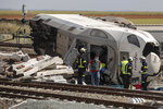 Firefighters and Spanish civil guards at the scene of an accident after a high-speed passenger train hit a car on a track in La Hiniesta, northwest Spain, Tuesday, June 2, 2020. Two people were killed when a high-speed passenger train with more than 150 people on board hit a car on the tracks in northwest Spain on Tuesday. (AP Photo/Emilio Fraile)