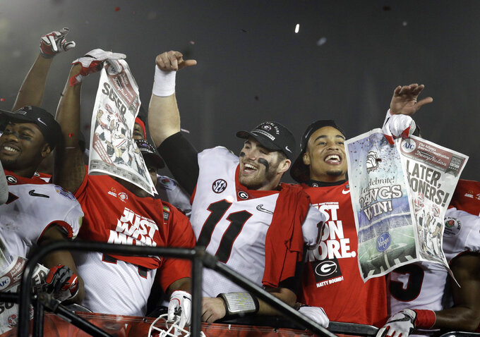 FILE - In this Jan. 1, 2018 file photo Georgia players hold up newspapers as they celebrate after they defeated Oklahoma 54-48 in overtime in the Rose Bowl NCAA college football game in Pasadena, Calif. A year ago, Georgia was getting ready for the College Football Playoff. Now, it feels like the Bulldogs are preparing for the Letdown Bowl. The team missed out on the four-team playoff field after another bitter loss to Alabama, forcing it to settle for the Sugar Bowl as a consolation prize. (AP Photo/Jae C. Hong, file)