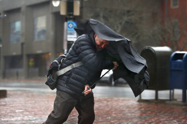 A man battles heavy rain and gusty winds during a winter storm, Thursday, Feb. 27, 2019, in Portland, Maine. The storm, which has caused power outages, is expected to dump up to 10 inches of snow in parts of the state while the coast will receive only rain. (AP Photo/Robert F. Bukaty)