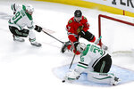 Dallas Stars goaltender Anton Khudobin (35) makes a save on a shot by Chicago Blackhawks' Kirby Dach (77) as Tyler Seguin also defends during the second period of an NHL hockey game Tuesday, Nov. 26, 2019, in Chicago. (AP Photo/Charles Rex Arbogast)