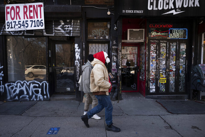FILE - In this Feb. 8, 2021, file photo, a man walks by an empty retail store, left, that is available for rent during the coronavirus pandemic in New York. State governments will get a big influx of federal money from the $1.9 trillion COVID-19 relief package that could suddenly enable them to undertake large, expensive projects that have long been on their to-do lists, including high-speed internet for rural areas and drinking water improvements. (AP Photo/Mark Lennihan, File)