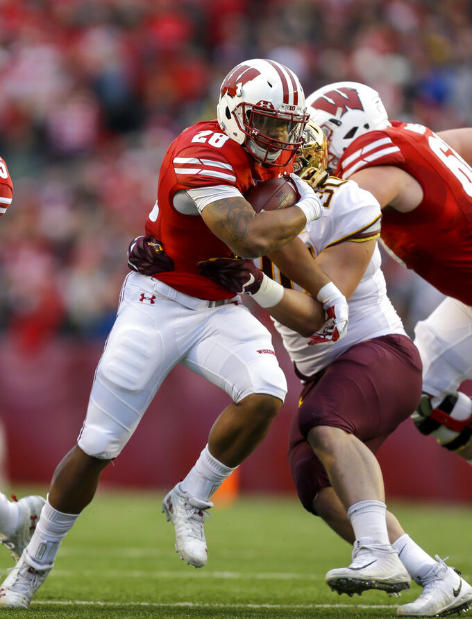 Wisconsin running back Jonathan Taylor runs against Minnesota defensive lineman Alex Reigelsperger (30) during the first half of an NCAA college football game Saturday, Nov. 24, 2018, in Madison, Wis. (AP Photo/Andy Manis)