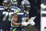 Seattle Seahawks wide receiver DK Metcalf reads a birthday note handed him by his teammates after he scored a touchdown against the New York Jets during the first half of an NFL football game, Sunday, Dec. 13, 2020, in Seattle. (AP Photo/Lindsey Wasson)