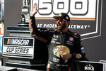 Martin Truex Jr waves to fans from Victory Lane after winning a NASCAR Cup Series auto race at Phoenix Raceway, Sunday, March 14, 2021, in Avondale, Ariz. (AP Photo/Ralph Freso)