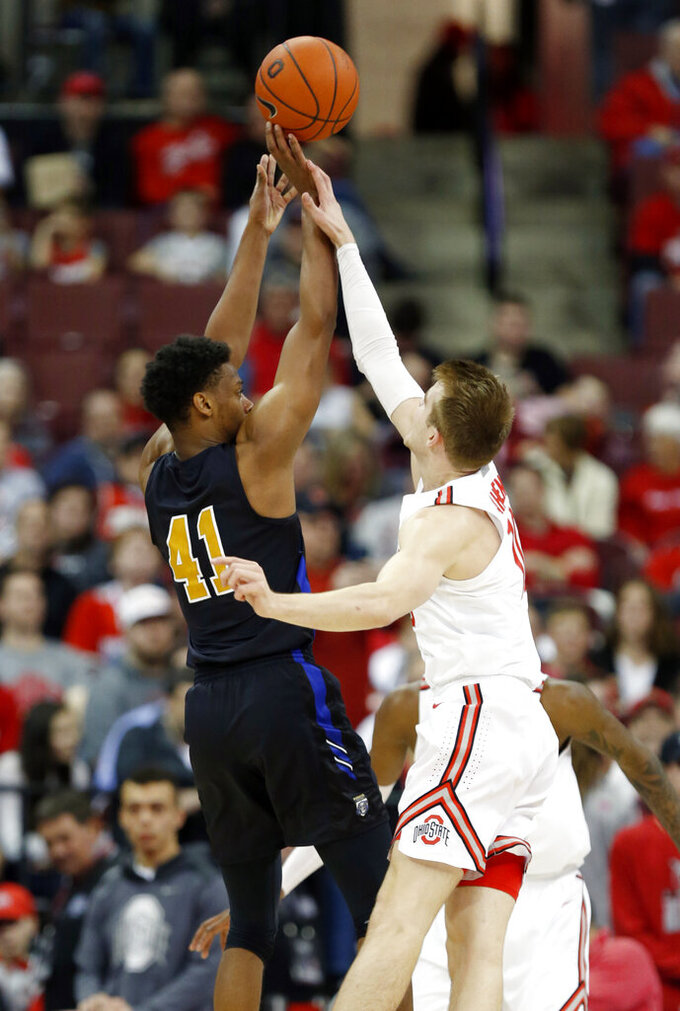 Purdue Fort Wayne guard Marcus DeBerry, left, goes up for a shot in front of Ohio State forward Justin Ahrens during the second half of an NCAA college basketball game in Columbus, Ohio, Friday, Nov. 22, 2019. Ahrens was called for a foul on the play. Ohio State won 85-46 (AP Photo/Paul Vernon)