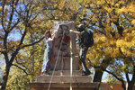FILE - In this Saturday, Oct. 12, 2020, file photo, demonstrators secure a rope around the centerpiece of a solid stone obelisk before tearing it down in Santa Fe, N.M. The Hispanic cultural association Union Protectiva de Santa Fe sued the city's mayor Wednesday, June 16, 2021, over the destruction of the obelisk by activists last year and plans to move the memorial permanently. The lawsuit argues that the obelisk, which honors Hispanic soldiers that fought and died for the Union in battles with Confederate soldiers and Indigenous tribes, is a protected historical site. (AP Photo/Cedar Attanasio, File)