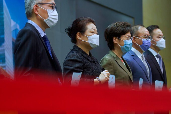 Hong Kong Chief Executive Carrie Lam, center, poses with other officials before a press conference in Hong Kong, Tuesday, April 13, 2021. Lam said Tuesday that Hong Kong's legislative elections would take place in December, more than a year after they were postponed last year with authorities citing public health risks from the coronavirus pandemic. (AP Photo/Vincent Yu)