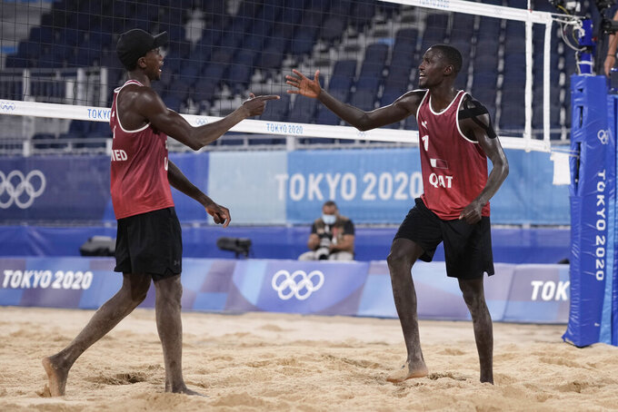 Cherif Younousse, right, of Qatar, and teammate Ahmed Tijan celebrate a play during a men's beach volleyball quarterfinal match against Italy at the 2020 Summer Olympics, Wednesday, Aug. 4, 2021, in Tokyo, Japan. (AP Photo/Petros Giannakouris)