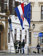 A police officer on a ladder inspects the site of a shooting in Zagreb, Croatia, Monday Oct. 12, 2020. A gunman on Monday shot and wounded a police officer outside the Croatian government headquarters in the capital, Zagreb, before killing himself, police said. The shooting happened around 8 a.m. at Trg Svetog Marka, or St. Mark's Square, which hosts the Croatian parliament building and other other important state institutions. (AP Photo/Darko Bandic)