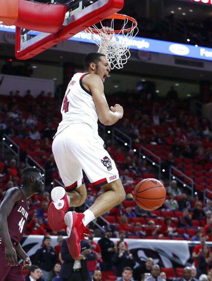 North Carolina State's Jericole Hellems (4) celebrates a dunk against Arkansas-Little Rock during the first half of an NCAA college basketball game at PNC Arena in Raleigh, N.C., Saturday, Nov. 23, 2019. (Ethan Hyman/The News & Observer via AP)