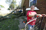 Cecil Gott takes a break from removing a fallen tree in a neighbor's yard, Friday, Aug. 14, 2020, in Cedar Rapids, Iowa. The storm that struck Monday morning left tens of thousands of Iowans without power as of Friday morning. (AP Photo/Charlie Neibergall)
