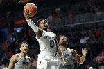 Miami guard Chris Lykes (0) goes up for a shot against Wake Forest forward Ody Oguama (33) and guard Andrien White (13) during the first half of an NCAA college basketball game, Saturday, Feb. 15, 2020, in Coral Gables, Fla. (AP Photo/Wilfredo Lee)