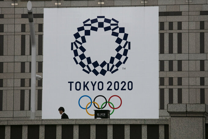 A man walks past a large banner promoting the Tokyo 2020 Olympics in Tokyo, Monday, March 23, 2020. The International Olympic Committee on Tuesday postponed this summer's Tokyo Games for a year as coronavirus deaths mounted around the world and U.S. lawmakers closed in on a nearly $2 trillion deal to help cushion the economic damage from the crisis. (AP Photo/Jae C. Hong)