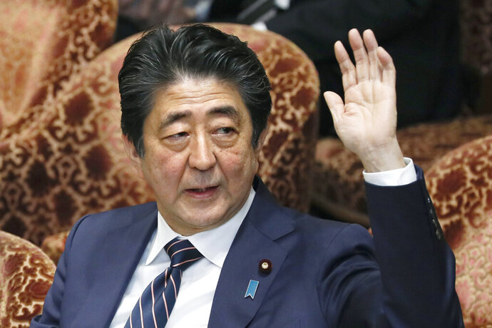 """Japanese Prime Minister Shinzo Abe raises his hand during a parliamentary session at the Lower House in Tokyo, Monday, Feb. 18, 2019. Abe and his chief spokesman have declined to say if Abe nominated President Donald Trump for a Nobel Peace prize. Speaking in parliament on Monday, Abe said the Nobel committee has never in a half-century disclosed the identity of the person or groups behind such nominations. He said, """"I thus decline comment.""""(Kyodo News via AP)"""
