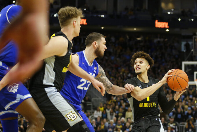 Marquette's Brendan Bailey drives to the basket against Seton Hall's Sandro Mamukelashvili (23) drives to the basket during the first half of an NCAA college basketball game Saturday, Feb. 29, 2020, in Milwaukee. (AP Photo/Aaron Gash)