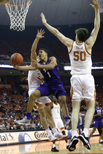 FILE - In this Feb. 19, 2020, file photo, TCU guard Desmond Bane (1) drives past Texas center Will Baker (50) and forward Brock Cunningham, left, during the first half of an NCAA college basketball game in Austin, Texas. Bane was selected to the Associated Press All-Big 12 first team announced Tuesday, March 10, 2020.(AP Photo/Eric Gay, File)