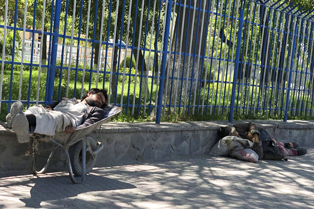In this May, 6, 2020, photo, beggars sleep on the side of the road in Kabul, Afghanistan, where there have been an increase in the number of beggars during the city lockdown for the coronavirus. (AP Photo/Rahim Faiez)
