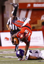 FILE - In this Aug. 30, 2018, file photo, Utah's Jason Shelley (15) is up ended by Weber State cornerback Parker Preator (20) in the second half of an NCAA college football game in Salt Lake City. The big question facing Utah when it hosts Oregon is whether Jason Shelley can pick up where Tyler Huntley left off. Shelley, a redshirt freshman, will make his first career start Saturday against the Ducks in place of Huntley, who broke his collarbone late in the third quarter of Utah's 38-20 loss last week to Arizona State. (AP Photo/Rick Bowmer, File)