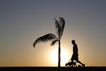 A man walks his dog as the sun sets in Asuncion, Paraguay, Saturday, Aug. 1, 2020, amid the new coronavirus pandemic. (AP Photo/Jorge Saenz)