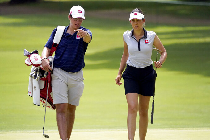 Albane Valenzuela, of Switzerland, and her brother and caddy, Alexis Valenzuela, walk across the 11th green during a practice round prior to the women's golf event at the 2020 Summer Olympics, Monday, Aug. 2, 2021, at the Kasumigaseki Country Club in Kawagoe, Japan. (AP Photo/Matt York)