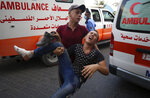 A protestor helps a wounded youth, who was shot by Israeli troops in his foot during a protest at the Gaza Strip's border with Israel, into the treatment room of Shifa hospital in Gaza City, Saturday, Aug. 21, 2021. (AP Photo/Abdel Kareem Hana)