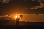 Birds fly as a man walks during a sunset in Alimos, a seaside suburb of Athens, on Tuesday, April 20, 2021. (AP Photo/Petros Giannakouris)