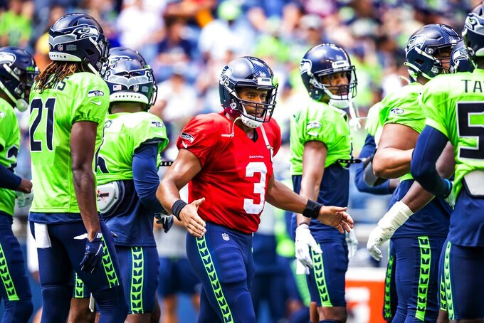 Seattle Seahawks quarterback Russell Wilson (3) greets the defense before playing a mock game as part of an NFL football training camp at Lumen Field in Seattle, Sunday, Aug. 8, 2021. (Bettina Hansen/The Seattle Times via AP)
