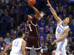 Texas A&M's Savion Flagg (1) shoots between Kentucky's Jemarl Baker (13) and Reid Travis (22) during the second half of an NCAA college basketball game in Lexington, Ky., Tuesday, Jan. 8, 2019. Kentucky won 85-74. (AP Photo/James Crisp)