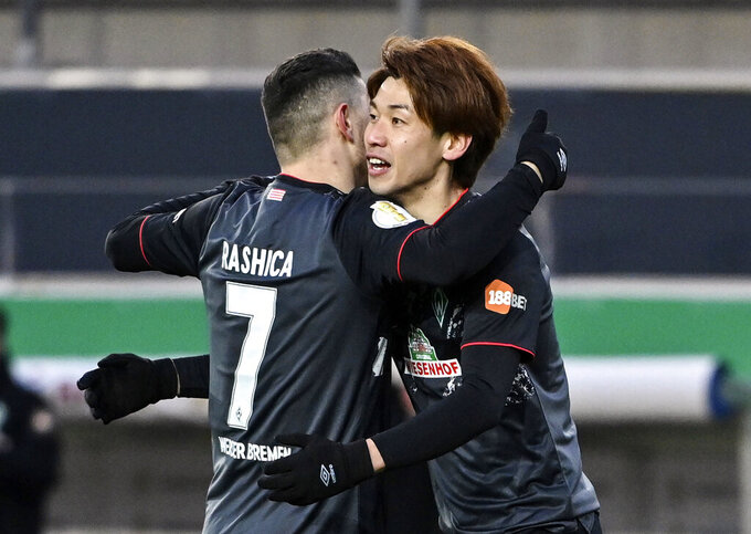 Bremen's Yuya Osako, right, celebrates with teammate Milot Rashica after scoring during the German soccer cup quarter final soccer match between Jahn Regensburg and Werder Bremen at Jahnstadion Regensburg in Regensburg, Germany, Wednesday, April 7, 2021. (Armin Weigel/dpa via AP)