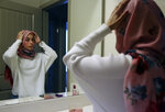 Amirah Ahmed, 17, adjusts her hijab before leaving for the grocery store on Saturday, Aug. 14, 2021, in Fredericksburg, Va. (AP Photo/Jessie Wardarski)
