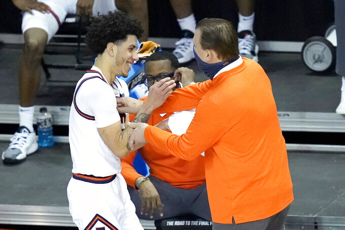 Illinois guard Andre Curbelo, left, celebrates with head coach Brad Underwood during the second half of a first round NCAA college basketball tournament game against Drexel Friday, March 19, 2021, at the Indiana Farmers Coliseum in Indianapolis. Illinois won 78-49. (AP Photo/Charles Rex Arbogast)