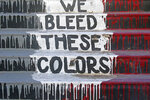 "The phrase ""We Bleed These Colors"" is shown along a walkway which leads from the Bountiful High School parking lot up to the football field Tuesday, July 28, 2020, in Bountiful, Utah. While advocates have made strides in getting Native American symbols and names changed in sports, they say there's still work to do mainly at the high school level, where mascots like Braves, Indians, Warriors, Chiefs and Redskins persist. (AP Photo/Rick Bowmer)"